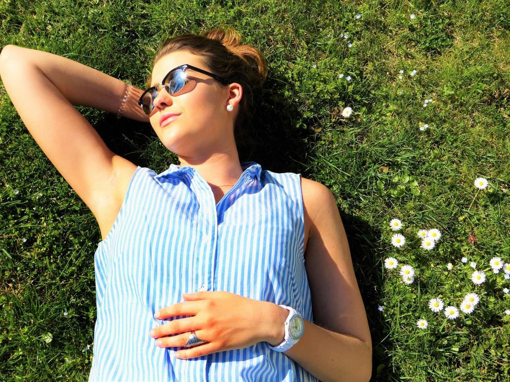 Frau liegt in der Sonne im Gras