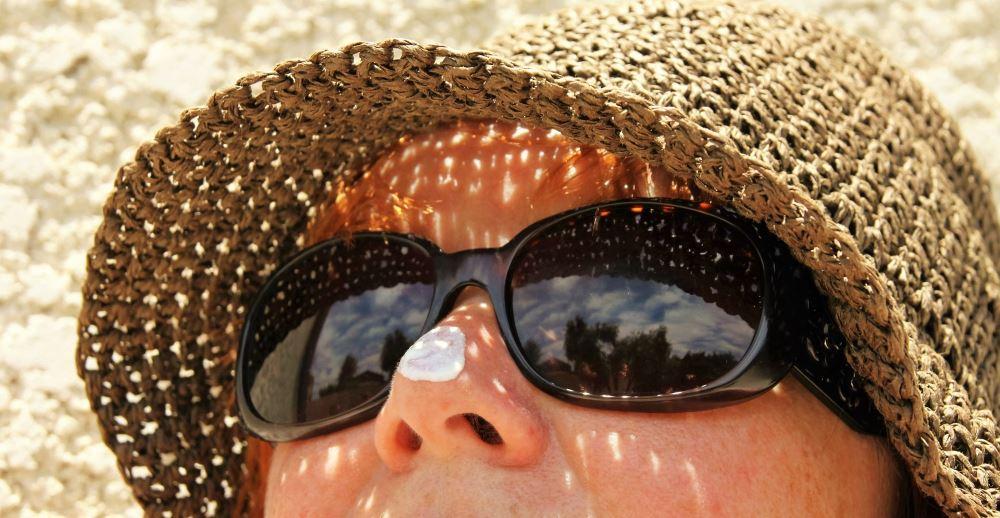 Frau mit Sonnenhut, Sonnenbrille und Sonnencreme, Hautschutz
