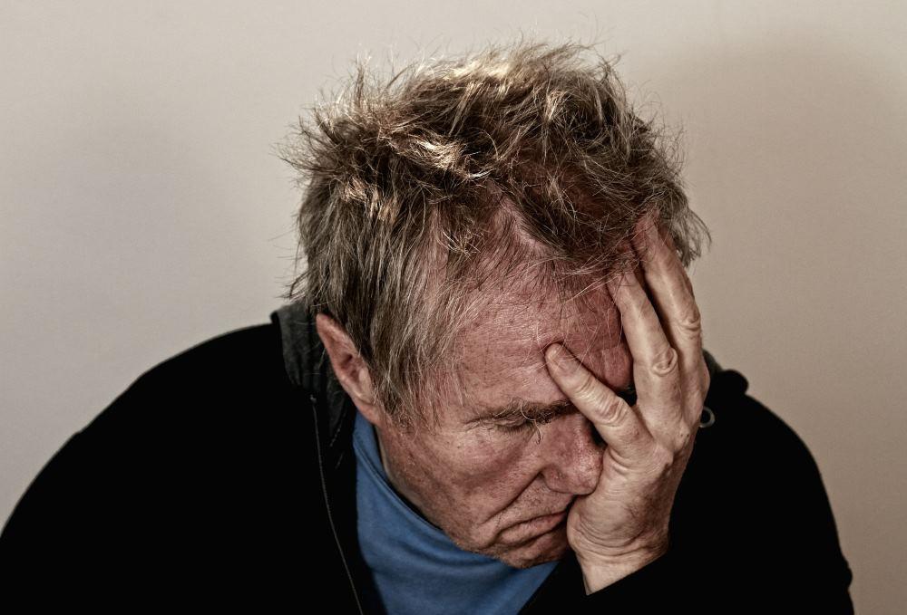 Mann mit Kopfschmerzen im Urlaub