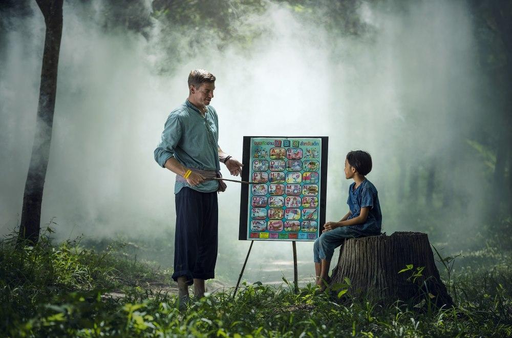 Lehrer auf Tafel im Wald mit Schülerin