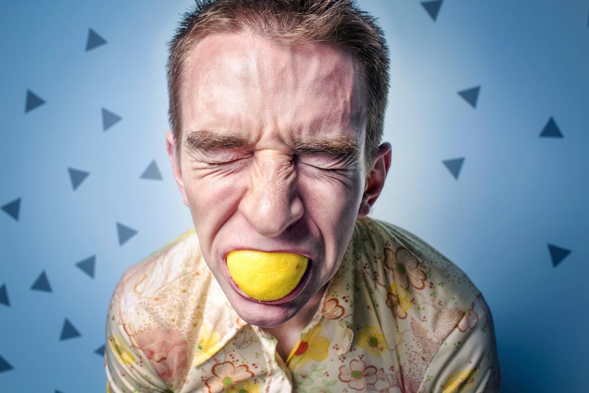 Mann mit Zitrone im Mund