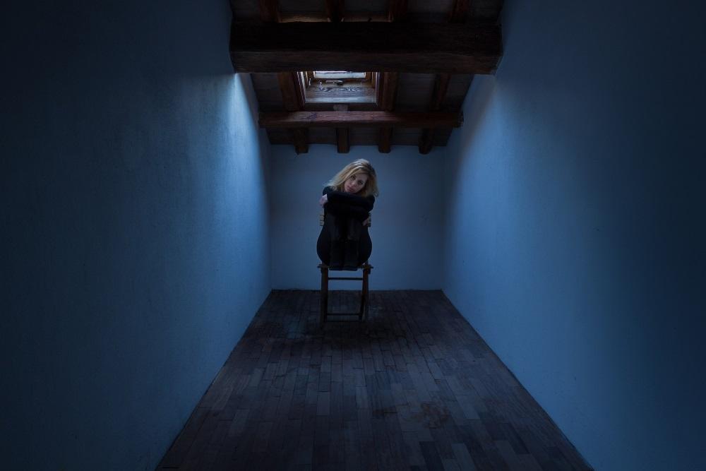 Frau sitzt auch einem Sessel in einem dunklen Raum